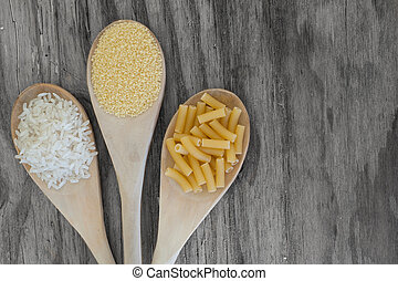 rice, couscous and macaroni on wooden background