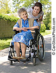 senior woman outdoors - Senior woman in a wheelchair with...