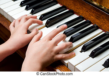 Child hands playing piano - Llittle girl trying to play the...