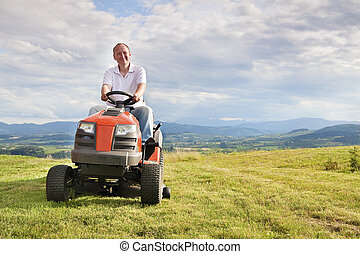Man riding a lawn tractor - Man mowing his lawn on a riding...