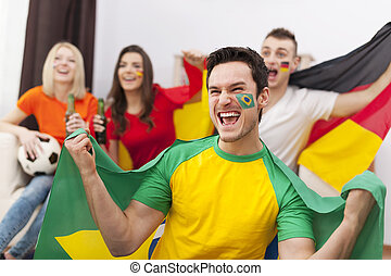 Excited brazilian man with her friends cheering football...