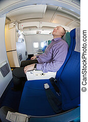 Businessman resting on a airplane - Man resting on a plane