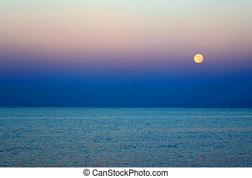 Moon that rises above the blue sea at nightfall - full Moon...