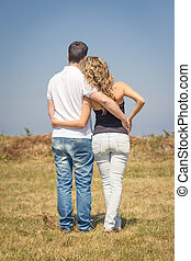 Love couple embracing outdoors on a summer day - Back view...