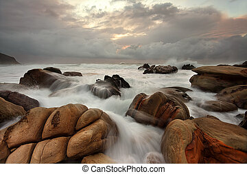 Ocean surges over weathered rocks - The ocean surges over...