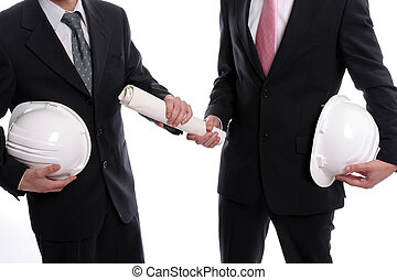 detail of two business man with safety hats, exchanging a...