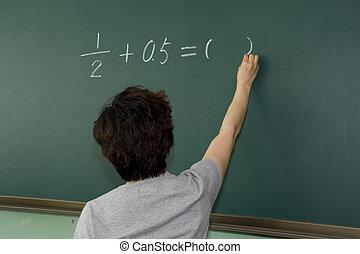Teacher in front of blackboarder - Female teacher writing on...