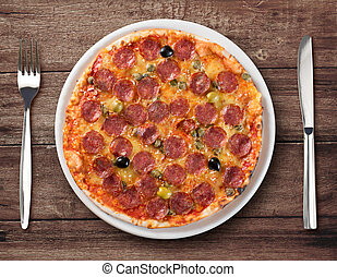 Italian salami pizza top view on plate with fork and knife