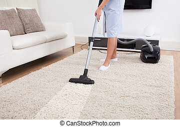 Maid Cleaning Carpet With Vacuum Cleaner - Cropped image of...