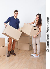 Young Couple Carrying Cardboard Boxes At New Home - Full...
