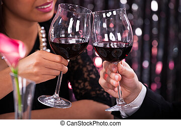 Couple Toasting Wineglasses In Restaurant - Cropped image of...