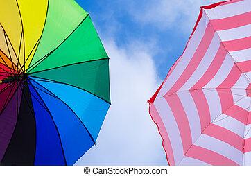 Beach umbrellas background against a blue sky