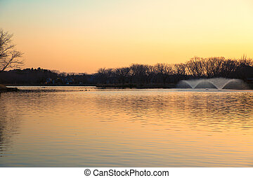 Sunset of the pond with fountains