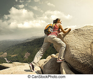 Hiker with backpack crossing rocky terrain.