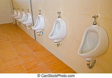 Old white porcelain urinals in public toilets
