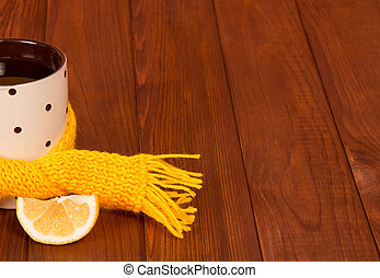 Cup of tea with lemon tied scarf on wooden table background...