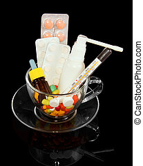 Glass cup filled medicines isolated on a black background