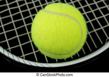 Tennis racket and tennis bal on black background