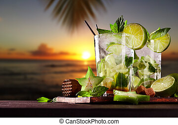 Fresh mojito cocktails on beach - Mojito drinks on wood with...