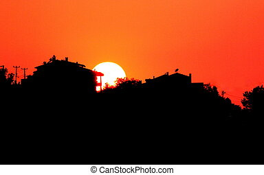 Sunset with town silhouette.