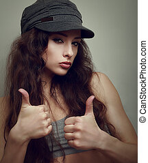 Happy joy teen girl in fashion cap with thumb up sign...