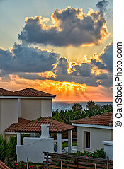 Sunset over holiday beach villas - Sunset with sunbeams over...