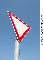 Sign - Yield traffic sign against clear blue sky
