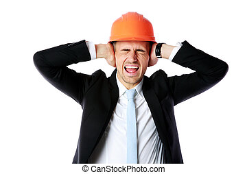 Businessman in helmet covering his ears over white...