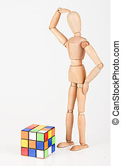 Confused wood mannequin stand next to puzzle confused before attempt to solve it