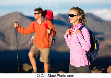Hikers enjoying the view from the mountain top - Two hikers...