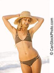 Beautiful girl on the beach at sunset in bikini