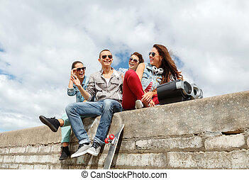 group of smiling teenagers hanging out - summer holidays and...