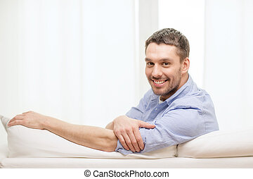 smiling man sitting on sofa at home - home and happiness...