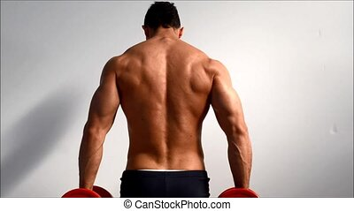 Young bodybuilder training traps and shoulders with...
