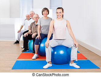 People Sitting On Fitness Balls In Exercise Class - Portrait...