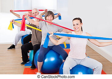 People With Resistance Bands Sitting On Fitness Balls -...