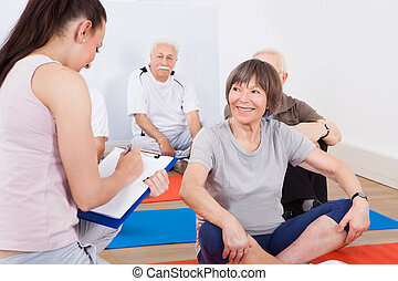 Trainer Taking Notes From Senior Customers - Young female...