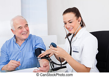 Doctor Measuring Blood Pressure Of Senior Man - Happy female...
