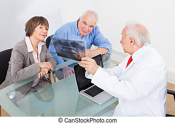 Dentist Explaining X-Ray To Senior Couple