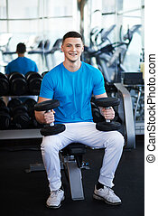 Young sports guy sitting on bench with a dumbbell - Young...