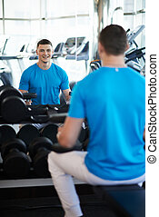 Young sports guy sitting on bench with a dumbbell