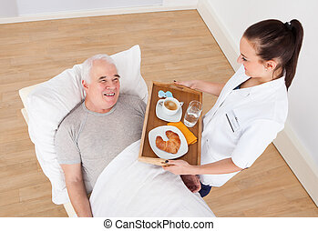 Doctor Serving Breakfast To Senior Man