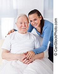 Caretaker With Senior Man At Nursing Home - Portrait of...