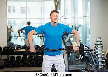 man doing exercises with barbell in gym