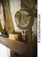 Vintage Amish hat hanging frome pole with shelf with jars in...