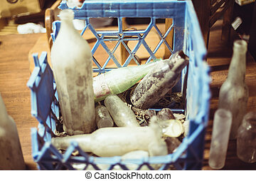 old crate filled with glass bottles - old broken blue crate...