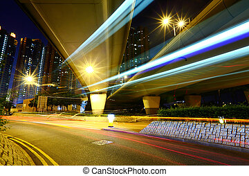 Fast moving car light in city at night