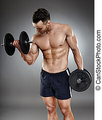 Athletic man working out with dumbbells - Monochrome shot of...