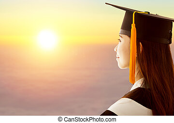 female graduation is thinking future with sunset background...