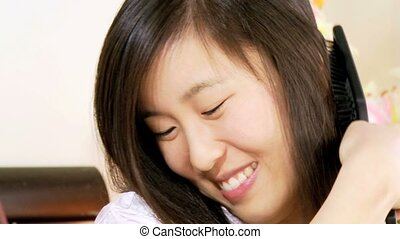 Chinese girl brushing long hair - Dolly shot of happy asian...